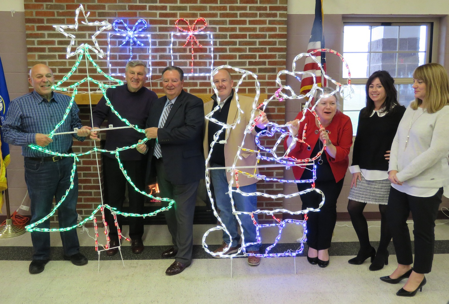 From left, Assemblyman Angelo Morinello, Jerry Wolfgang, Town of Niagara Supervisor Lee Wallace, Chris Woods, Janiene Ennis-Garcia, Meghan Ayers and Suzanne Kennedy pose with some of the lighting displays for this year's `Noel at Niagara.` (Photo by David Yarger)