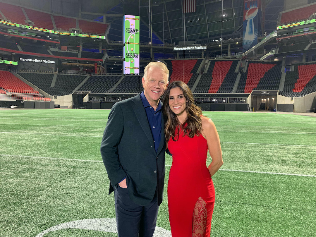 Boomer Esiason, analyst for CBS Sports' NFL pregame show `The NFL Today,` and Daniela Ruah, star of CBS' `NCIS: Los Angeles,` return to host a new CBS special celebrating 20 years of the Super Bowl's best commercials. They are shown as a past year's event from the Mercedes-Benz Stadium in Atlanta, home of Super Bowl LIII. (©2019 CBS Broadcasting Inc. All rights reserved.)
