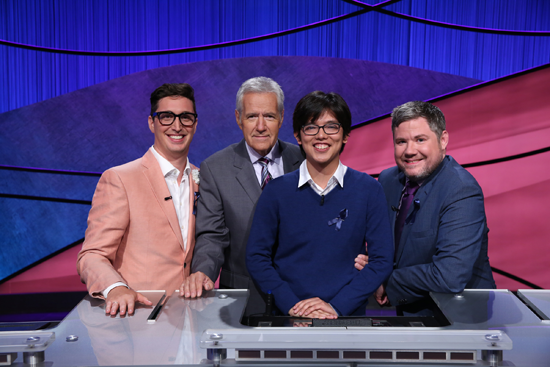`Jeopardy!` contestants Buzzy Cohen, Alan Lin and Austin Rogers (with host Alex Trebek) will return for a special tag-team tournament in 2019. (Photo courtesy of Jeopardy Productions Inc.)