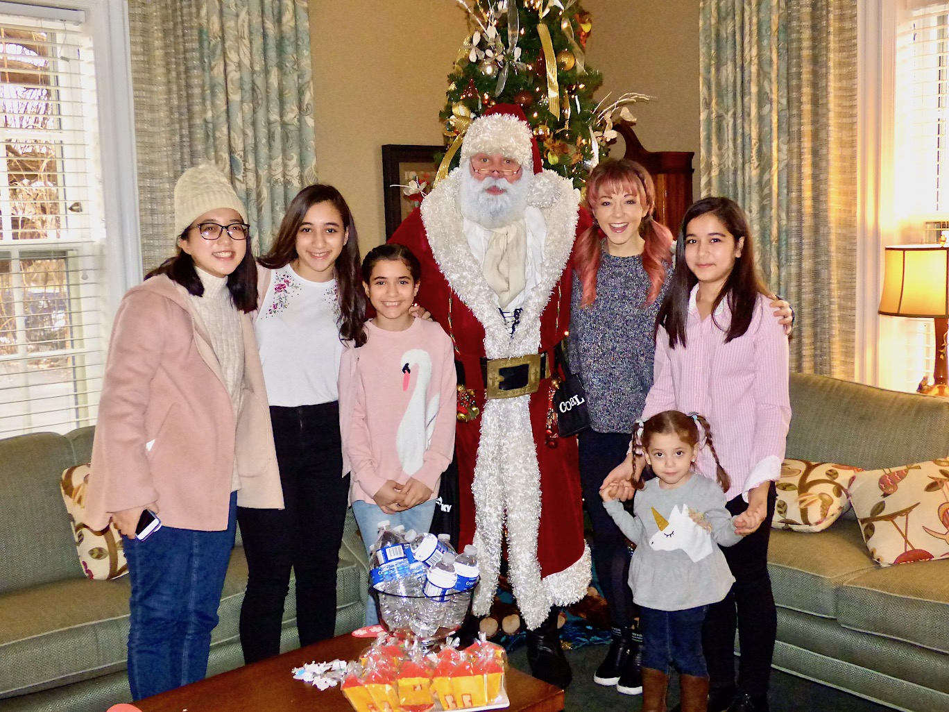 Lindsey Stirling is shown with Santa Claus, Jana Said and Jana's family.