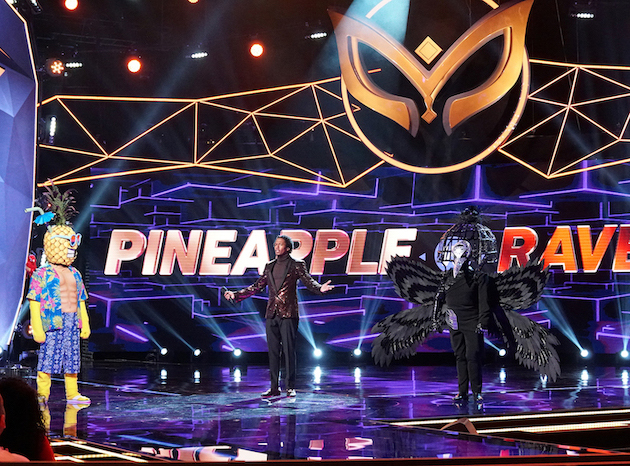`The Masked Singer`: From left, Pineapple, host Nick Cannon, and Raven. (Photo: © 2019 FOX Broadcasting/credit: Michael Becker/FOX)