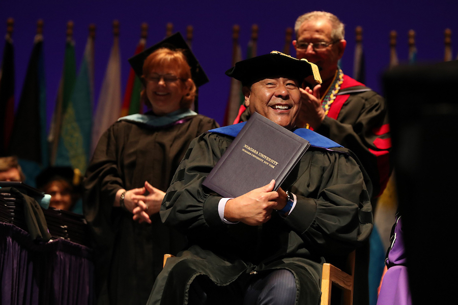 ABC's John Quiñones proudly displays the honorary doctorate he received during Niagara University's undergraduate commencement ceremony on May 12.