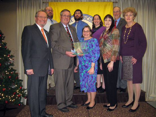 Pictured, front row: New York State Ag and Markets Commissioner Richard Ball congratulates Jim Bittner on his award. Also pictured: Margo Sue Bittner, NY Farm Bureau Representative Sandy Prokop, NY AG Society President Beth Claypoole; (back row): Kevin Bittner, David Bittner, Janet Walker, Award Committee Chairman Richard Church.