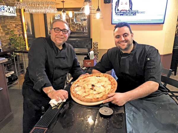 Jack and Charlie Soldano hold the margherita pizza they made from scratch at Casa Antica. The pie is fresh-made dough topped with homemade sauce, mozzarella molded from cheese curd, fresh basil and oil. The restaurant is located at 490 Center St., Lewiston.