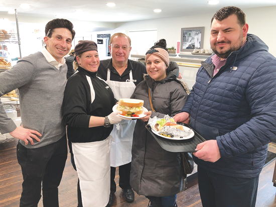 Pictured at Como on Center, Dominic Colucci, Dawn Antonacci and Louie Antonacci pose with customers Melissa Morinello and her husband, Joseph Genovese. Before the couple enjoyed sandwiches, Morinello said this was her third trip this week.