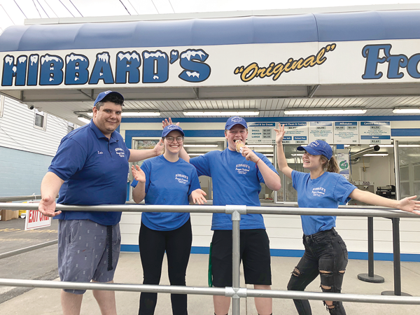 Pictured, from left, in front of the new railing, are employees Luis Olmedo, Taylor Nisbet, Justin Weinfurtner and Belle Wesser. Shown below, Belle serves a cone to Ian Sherman. (Photos by Joshua Maloni)