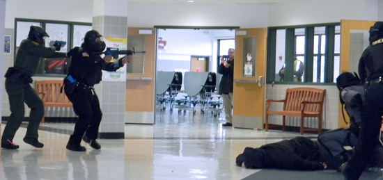 Officers encounter gunfire in a hallway search during Friday's active shooter drill.