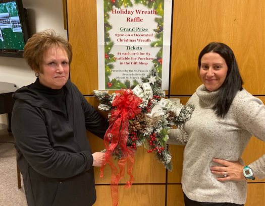 Maureen Sheeran, left, president of the St. Francis Guild of Mount St. Mary's Hospital, and Christina Lapsley, manager of volunteer services, show off a holiday wreath dressed with $500 cash, which will be raffled off Dec. 20. The wreath is displayed in the lobby of the hospital, where a holiday bazaar will take place Friday.