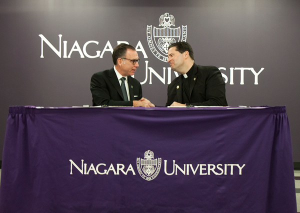 Paul J. Casseri, superintendent of the Lewiston-Porter Central School District, and the Rev. James J. Maher, C.M., president of Niagara University, shake hands after signing an agreement that offers international exchange students attending Lew-Port the opportunity to live in NU residence halls.