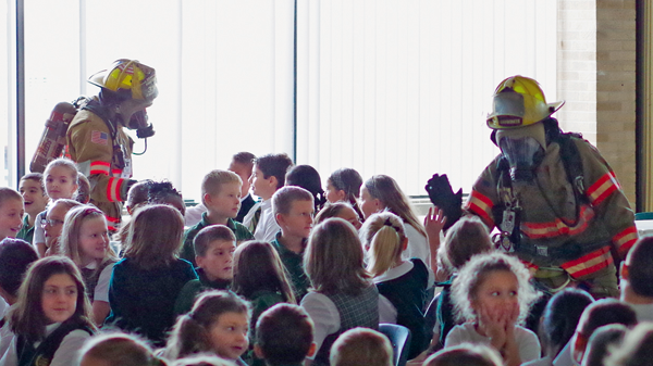 Grand Island firefighters in turnout gear greet the students at St. Stephen School. Students at the school held a fire safety assembly in the cafetorium before seeing the GIFC fire trucks. (Photo by Larry Austin)