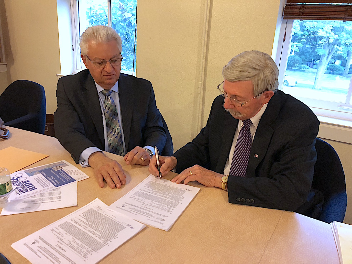 Village of Lewiston Mayor Terry Collesano signs the Frontier House purchase agreement as counsel Joseph Leone advises him on Monday.