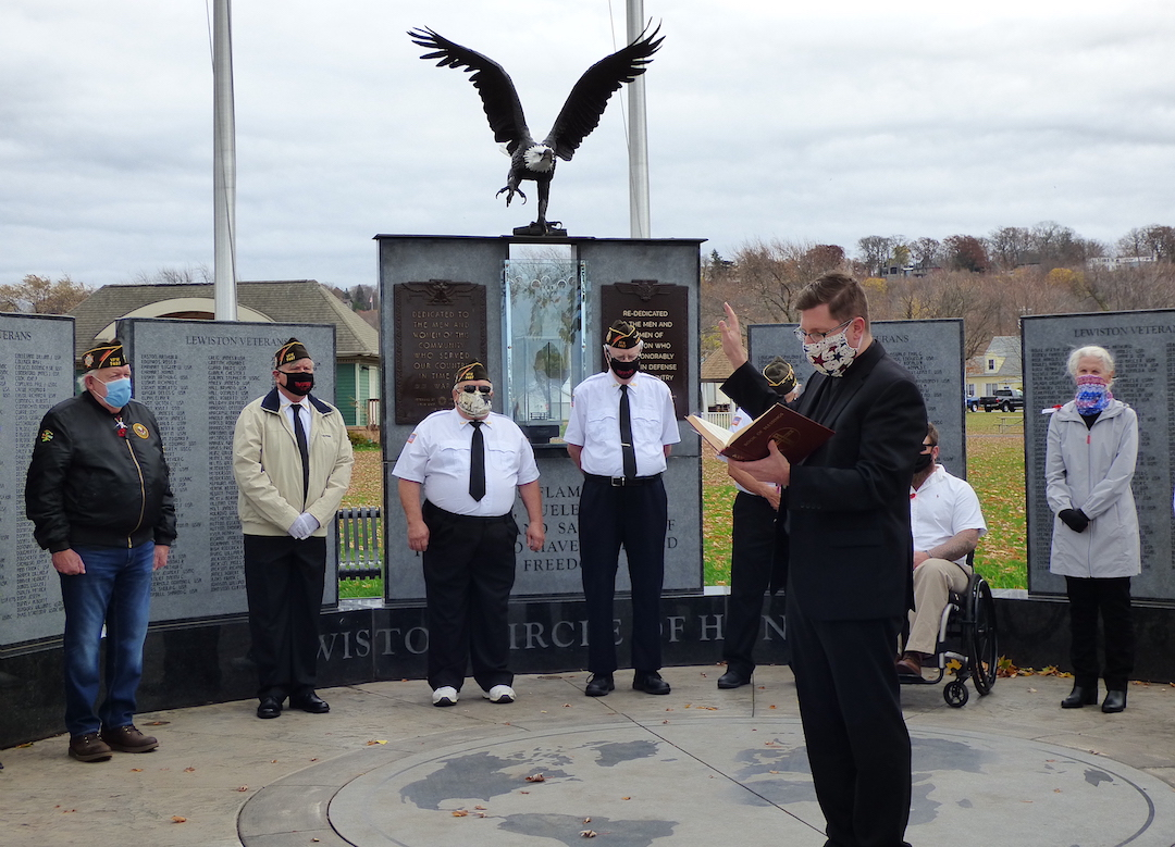 The Rev. Cole Webster of St. Peter R.C Church in Lewiston and St. Bernard in Youngstown blesses the `Circle of Honor` monument in Academy Park.