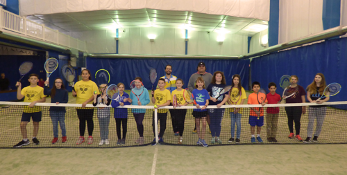 Tennis players line up for a photo following a recent practice session at the WTS court.