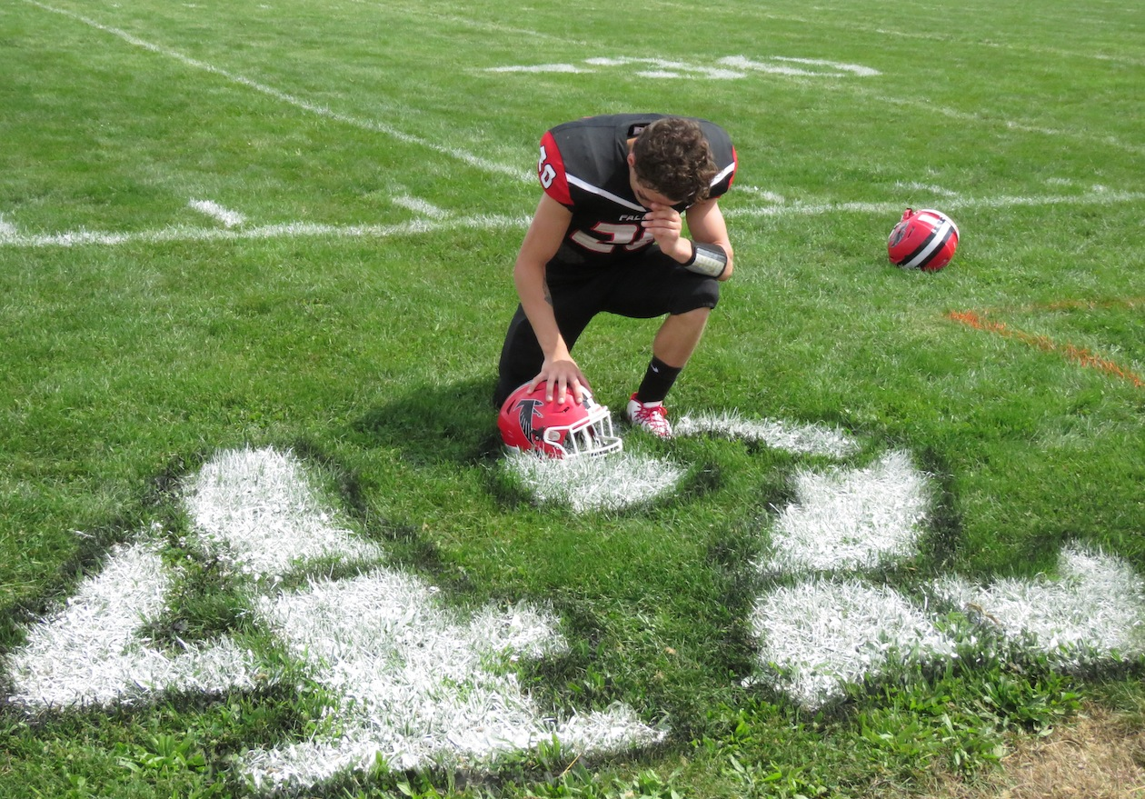 Niagara-Wheatfield's Jake DeWolf takes a knee by a paint No. 42 to remember the life of Michael Ziegler before the Falcons' opening football game versus North Tonawanda. N-W defeated the Lumberjacks, 48-0. (Photo by David Yarger)