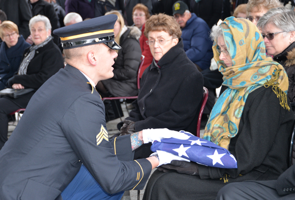 Sgt. Nicklaus Hilts presents a flag to a family member of Lawrence Ostwald during his burial at Gerald B.H. Solomon Saratoga National Cemetery in Schuylerville on Dec 15.
