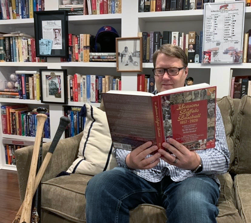 Brian Frank, an assistant editor of `The Seasons of Buffalo Baseball 1857-2020` and founder of herdchronicles.com enjoys his copy of the book this week.