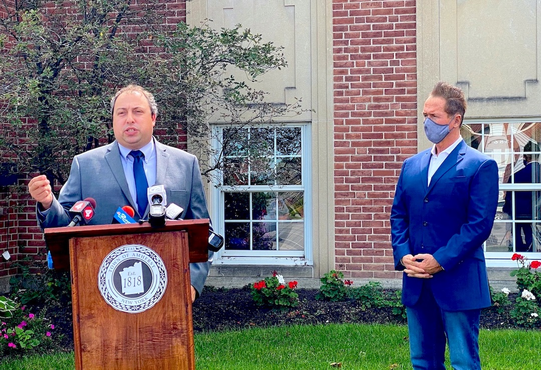 Congressman Brian Higgins watches as Town of Amherst Supervisor Brian Kulpa addresses the media.