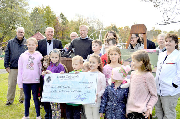 From left: Orchard Park Recreation Director Ed Leak, Orchard Park Supervisor Patrick Keem, Orchard Park Highway Superintendent Fred Piasecki, New York State Sen. Chris Jacobs, Orchard Meadows Playground Champion Kathleen McDonald, and neighboring children and families.