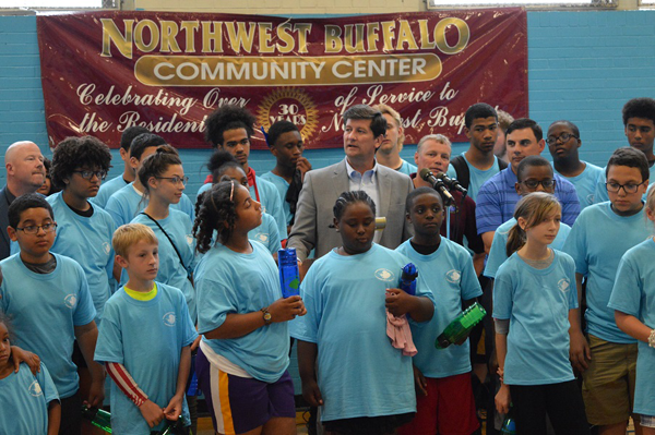 Erie County Executive Mark C. Poloncarz (center, in gray suit) joins Erie County Legislator Peter Savage (wearing blue striped shirt at Poloncarz' left) Northwest Buffalo Community Center Executive Director Larry Pernick, and some enthusiastic children to announce the beginning of `Operation Prime Time` summer programming at the center. Northwest Buffalo Community Center is one of 65 local not-for-profit agencies that received grant funding of up to $10,000 to offer enhanced summer programs and hours during the 10-week summer recess.