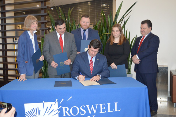 Erie County Executive Mark C. Poloncarz (seated) signs the Public Health Protection Act of 2018 into law at Roswell Park Comprehensive Cancer Center. Joining the County executive for the signing are, from left: Roswell Park Comprehensive Cancer Center President and CEO Candace Johnson, Ph.D.; Erie County Legislature Chairman Peter Savage; Assemblyman-elect Patrick Burke; Western Region Youth Advocate of the Year Zoe Kaminski; and Legislator John Bruso.