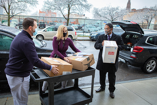 Special delivery: Praveen Arany, assistant professor of oral biology in the UB School of Dental Medicine (right) hands boxes of donated UB-made reusable face masks and face shields to Heather Mattiuzzo (center), Buffalo City Mission development and marketing, and Michael O'Hara, (left) Buffalo City Mission manager of major gifts. (Photo by Douglas Levere/University at Buffalo)