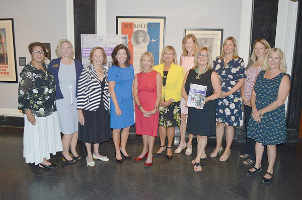 Executive Director of the Erie County Commission on the Status of Women Karen King (fourth from right, holding report) is joined by a host of current and former women elected officials, including Lt. Gov. Kathy Hochul (center, in blue), to announce the release of `Women in Elected Office: Challenges and Opportunities in Erie County,` a report detailing women's historical political participation and representation in both Erie County and local municipal governments and outlining a number of challenges women face in seeking and holding elected office.