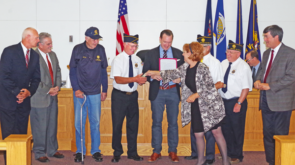 Councilwoman Beverly Kinney gives American Legion Grand Island Post No. 1346 Commander Ray DeGlopper a donation in exchange for a poppy during a Grand Island Town Board proclamation naming Sept. 8 and 9 as American Legion Patriot Poppy Days on the Island. On hand for the proclamation are, from left: councilmen Ray Billica and Chris Aronica; Garry Deutschlander and DeGlopper of Post No. 1346: Town Supervisor Nate McMurray; Kinney; Peter Kuszczak and Joe Mesmer of the GI Post; and Councilman Mike Madigan. (Photo by Larry Austin)
