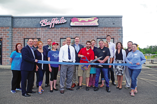 Buffalo Dog House Co-owner Mike Silla, with the chamber scissors, is flanked by co-owners Jeff Lyons (black shirt) and Jim Sheridan (white shirt) and manager Maddie Porter (blue) at the ribbon-cutting ceremony Tuesday for their new restaurant. Not pictured are co-owners Debbie Silla and Ken Yensan. (Photo by Larry Austin)