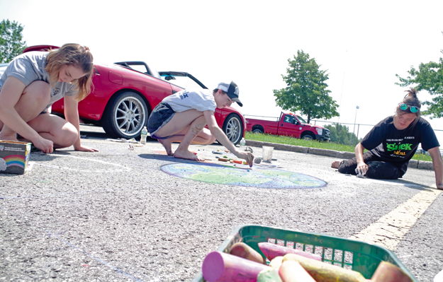 From left, Tess Lariviere, Julie Klein and Kelsey Mahoney of Grand Island High School practice a chalk mural Monday in preparation for the Chalk Walk competition at the Lewiston Art Festival. GIHS is the two-time defending champions of the event. (Photo by Larry Austin)