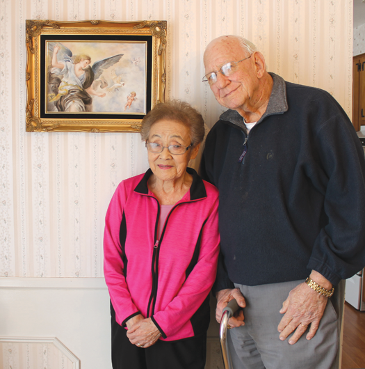 Chie Doring, pictured with her husband, Floyd, stands before one of her porcelain paintings that will be one of 20 displayed in an exhibit called `A Unique Asian Porcelain Art Show.` The exhibit will be held from 2 to 6 p.m. Sunday, April 26, at the Moose Lodge, 2524 Grand Island Blvd., Grand Island. There is no charge for the exhibition. (Photo by Karen Carr Keefe)