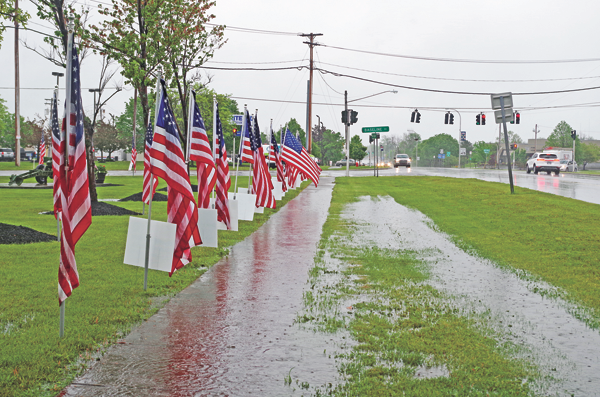 Thursday's lengthy showers flood the sidewalks at DeGlopper Park at the intersection of Baseline Road and Grand Island Boulevard, where the town holds its annual Memorial Day service. (Photo by Larry Austin)