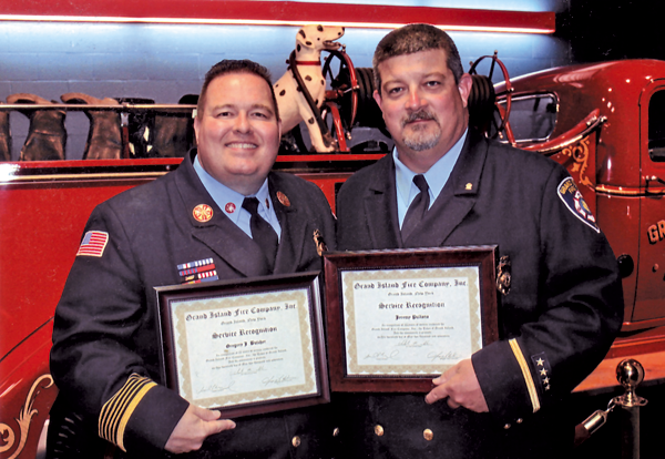 Greg Butcher and Jeremy Pullano proudly display their 25-year service awards from the Grand Island Fire Co.