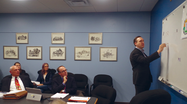 Town Supervisor Nathan McMurray draws on a white board in the Town Hall conference room as he tries to describe the difference between `design-build` and `design-bid-build` in building a new community center. (Photo by Larry Austin)