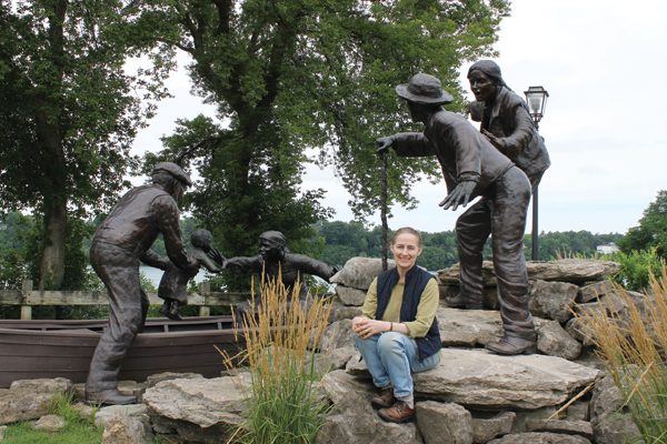 Sculptor Susan Geissler sits amid the figures of her Freedom Crossing Monument in Lewiston. She has been commissioned to sculpt the statue of World War II hero Charles N. DeGlopper that will be installed in the Grand Island park bearing his name. DeGlopper was killed in action in the battle of Normandy.