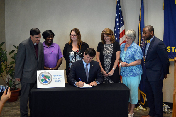 Erie County Executive Mark C. Poloncarz (seated) signs `Ruthie's Law,` a new local law designed to better protect senior citizens in nursing homes as well as provide current information to their loved ones and family members. Joining Poloncarz are, from left: Erie County legislators Peter Savage (3rd District) and Betty Jean Grant (2nd District), relatives of Ruth Murray, and Commissioner of Senior Services Tim Hogues (at right).