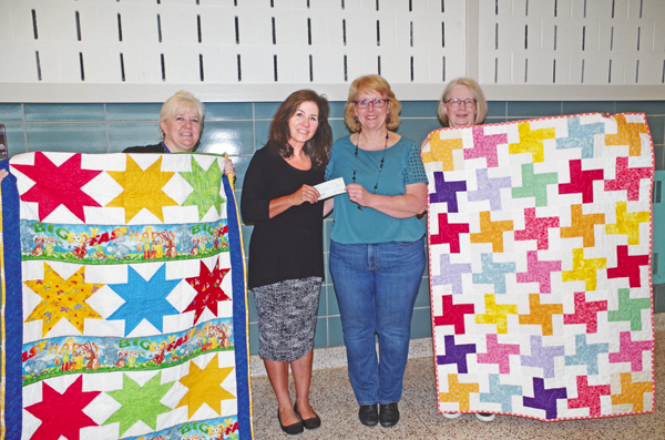 The River Lea Quilters Guild presented a $1,200 donation to Stone's Buddies, the first of two donations the guild will make with money raised from the group's quilt show, `Waves of Change.` Pictured, from left, are Susan Miles, president of the River Lea Quilters Guild, Joanne Koessler-Lana, director of Stone's Buddies, Kimberly Hall, co-chair with Janet Jackman of the quilt show, and Sandie Nethero, community service chairperson of the River Lea Quilters Guild. (Photo by Larry Austin)