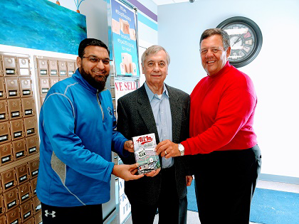 Islanders Fahim Mojawalla of the Island Ship Center, left, and Mike Billoni hold a copy of Ron Zoeller's new memoir, `All In.` (Photo by Larry Austin)
