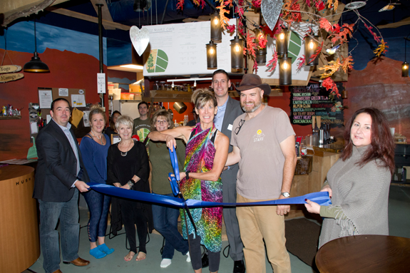 Sue Zinter, with the scissors, and Matt Green cut the ceremonial blue ribbon at the grand opening of Soma Cura's new beach salt room and revamped Alz Rootz Café on Oct. 27. Members of the Grand Island Chamber of Commerce were on hand for the event. (Photo by Larry Austin)