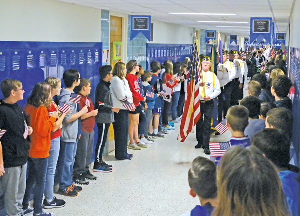 Ray DeGlopper leads a parade through the halls of Veronica Connor Middle School during an event honoring veterans. Students applauded as the parade made its way through the middle school and high school Monday morning. (Photo by Larry Austin)