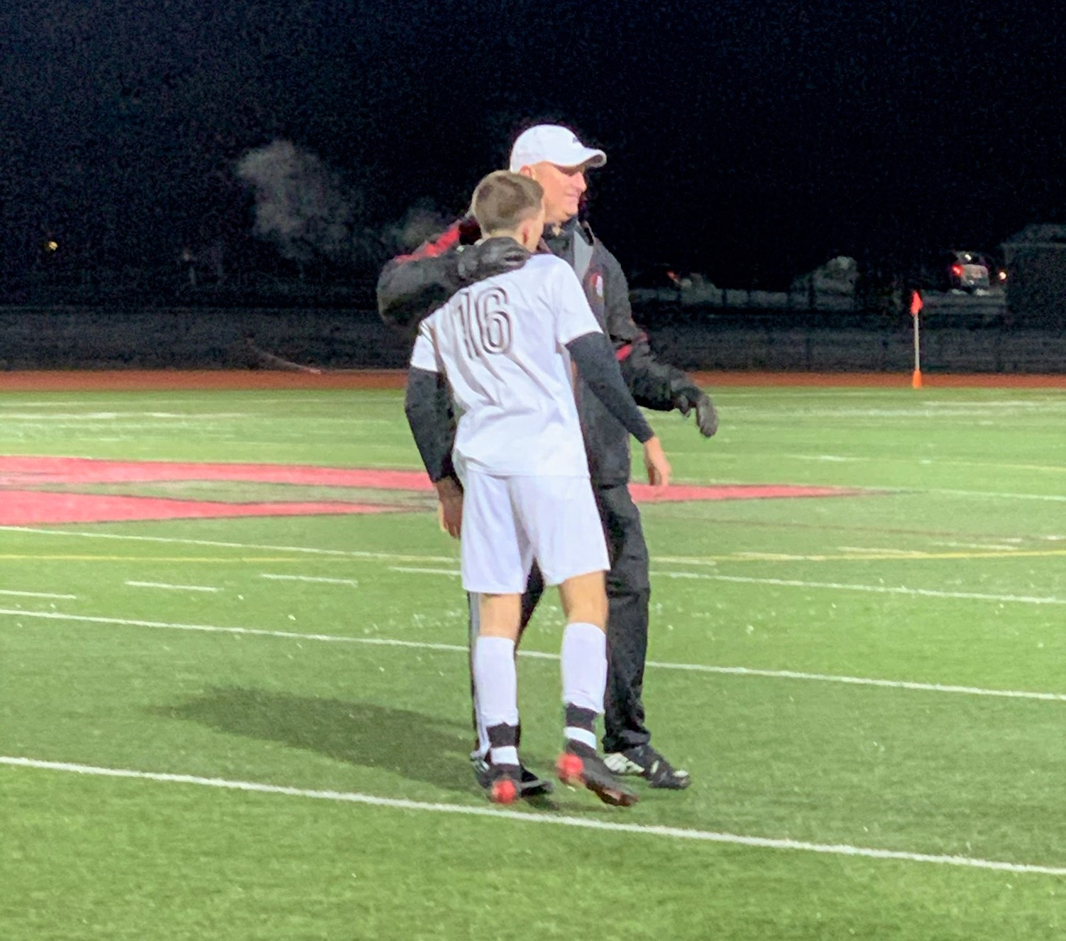 Niagara-Wheatfield Falcons coach John Coulter shares an embrace with senior Jake Vallas following the team's 3-0 loss in the Far West Regional. Vallas was the leading scorer for the Falcons and scored six goals in the postseason. (Photo by David Yarger)