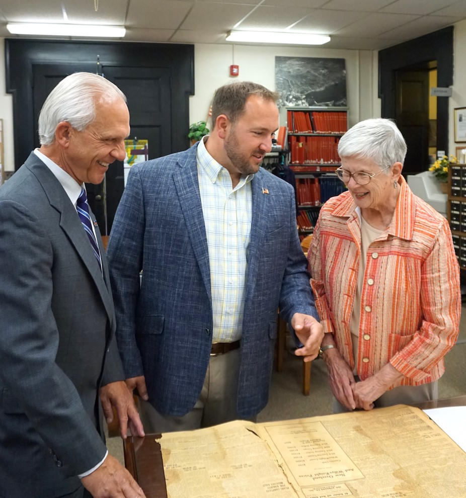 Niagara County Clerk Joseph A. Jastrzemski and Legislator Rich Andres show Christa Caldwell, a former Lockport librarian who serves on the Grigg-Lewis Foundation board of directors, brittle newspaper pages that have been digitally preserved by the Niagara County Historian's Office using a $51,000 grant from the foundation.