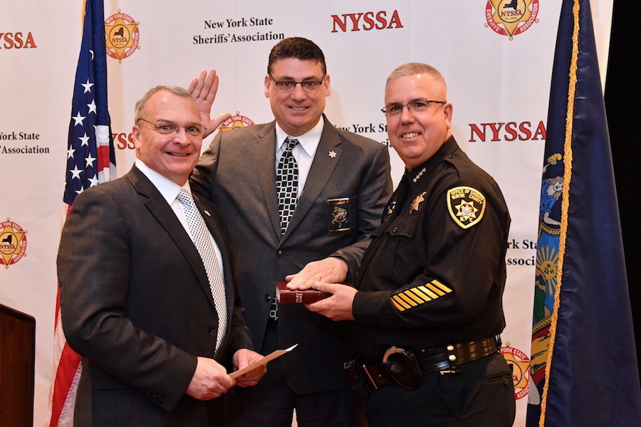 Niagara County Sheriff James Voutour (center) is sworn in as 1st vice chair of the executive committee of the New York State Sheriffs' Association. Performing the duties at the Association's 84th annual winter training conference are Wayne County Administrator Richard House (left) and newly elected President Sheriff Barry Virts (right).