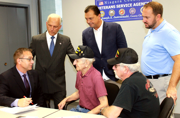 Niagara County Veterans Service Officer Chris Butler outlines benefits available to veterans for World War II veteran Frank Jastrzemski and Vietnam veteran Bill Paton during a trial run of a satellite veterans service agency office in North Tonawanda last month. Looking on are Niagara County Clerk Joseph A. Jastrzemski, Niagara County Legislature Majority Leader Randy R. Bradt and Legislator Rich Andres. Monthly veterans satellite hours begin Jan. 3.