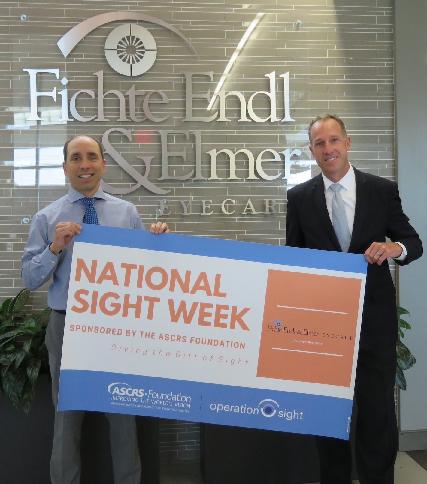 From left, Michael Endl M.D. and Thomas Elmer Jr. M.D. pose with the National Sight Week banner. (Photo by David Yarger)