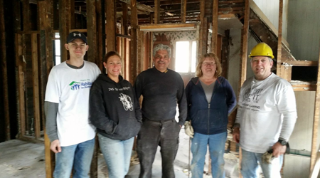 Ricardo Flores (center) stands with members of the Niagara Area Habitat for Humanity rehab team. (Photos by Lauren Garabedian)