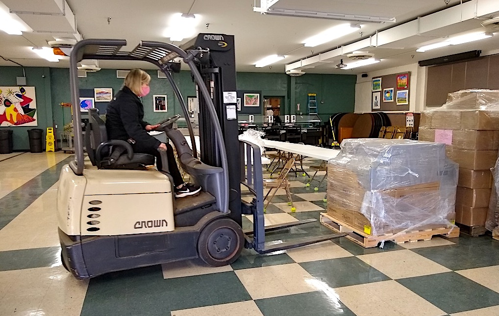 Pam Dixon runs the forklift moving the donation of food made to Heart, Love & Soul by The Church of Jesus Christ of Latter-day Saints.