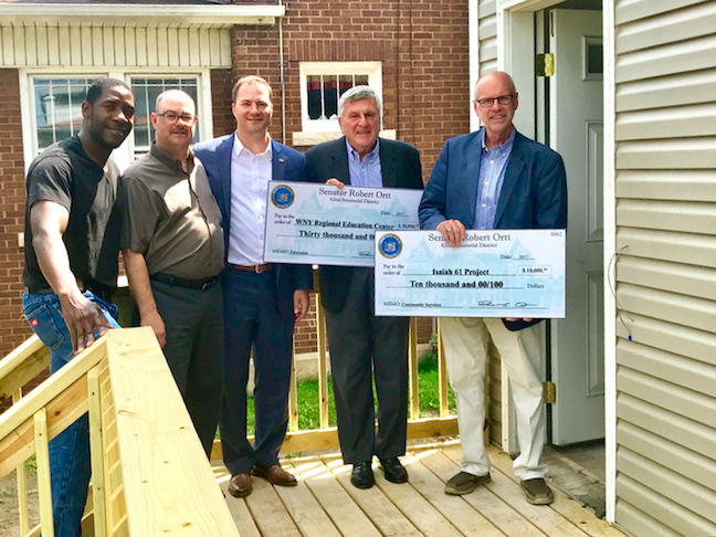 Pictured in front of the 16th Street home in Niagara Falls are, from left: Isaiah 61 Project graduate Austin Ofokansi, Isaiah 61 Project board President Mark Perkins, New York State Sen. Rob Ortt, WNY Regional Education Center Director Jerry Wolfgang and Isaiah 61 Project Executive Director Kevin Wing.