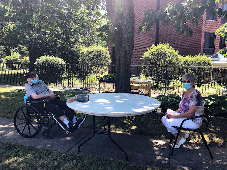 Schoellkopf Health Center resident Frank Coney, left, enjoys a visit from Sandy Basile on Friday in historic Schoellkopf Park. The occasion marked the first time they could visit since the onset of the COVID-19 pandemic.