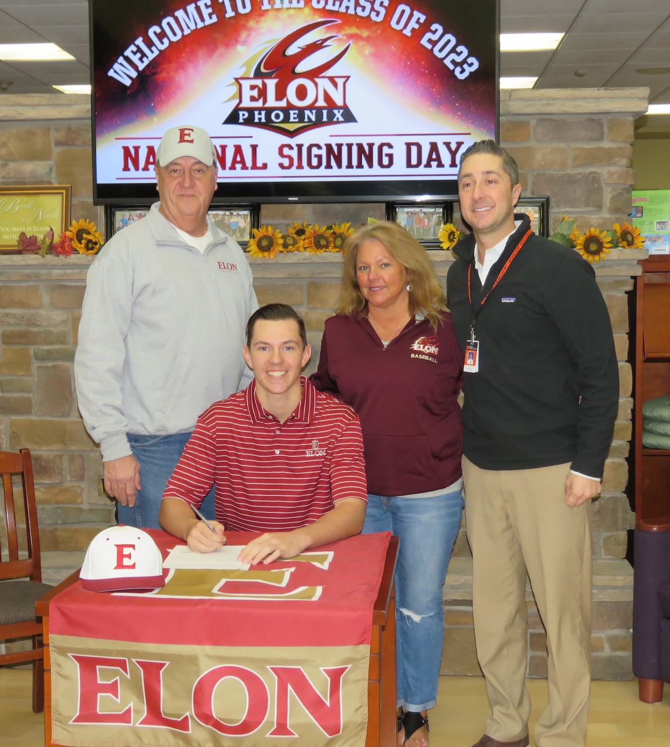 Ian Evans, sitting, signs his national letter of intent to play baseball at Elon University. Flanking Evans, from left, Lyle Evans, Diane Maggliazo and Wilson Athletic Director Jeff Roth. (Photos by David Yarger)