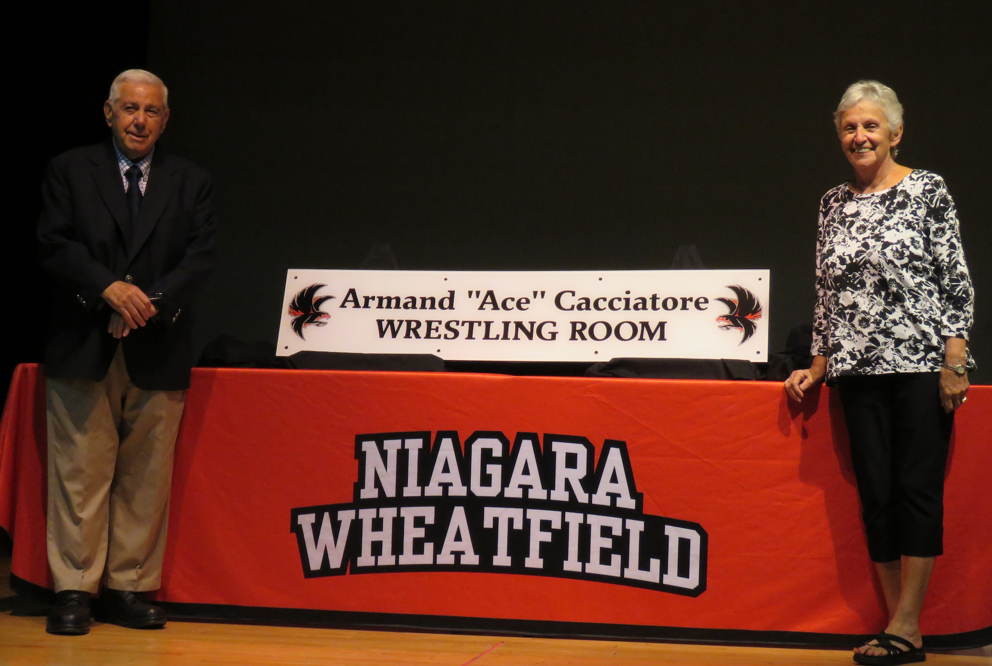 From left, Armand `Ace` Cacciatore and his wife, Mimi, pose with the new wrestling room sign dedicated in the coach's honor. (Photos by David Yarger)